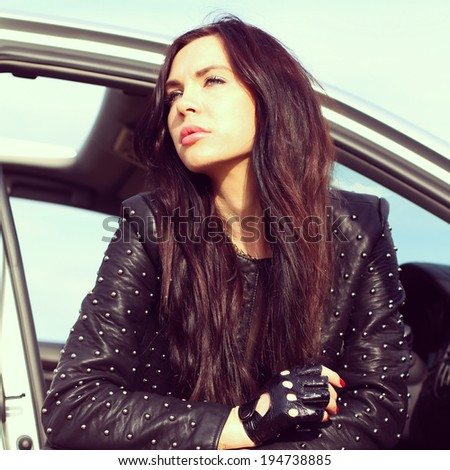 Portrait of a beautiful woman driving a sports car. - stock photo