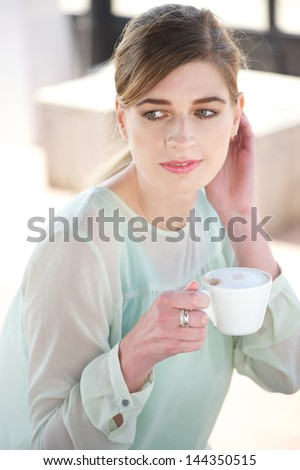 Portrait of a beautiful woman enjoying a cup of coffee outdoors - stock photo
