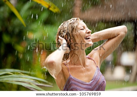 Portrait of a beautiful woman enjoying tropical rain falling on her in an exotic garden. - stock photo