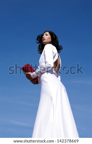 Portrait of a beautiful woman (fashion model) posing in elegant white atlas cocktail dress with red clutch in her hands over blue sky background. Copy-space. Outdoor shot - stock photo