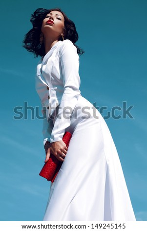 Portrait of a beautiful woman (fashion model) posing in elegant white atlas cocktail dress with red leather clutch in her hands over blue sky background. Sunny & cloudy weather. Outdoor shot - stock photo