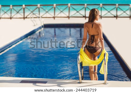 Portrait of a beautiful woman getting out of a swimming pool. beautiful long hair tanned female model posing by blue pool water. Outdoor summer portrait of sexy girl in sunglasses - stock photo