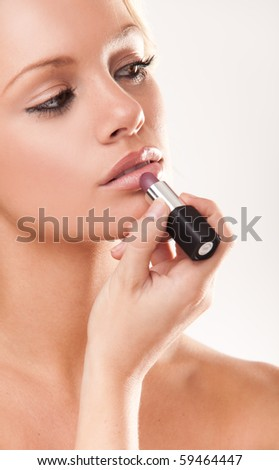 Portrait of a beautiful woman getting ready applying lipstick - stock photo