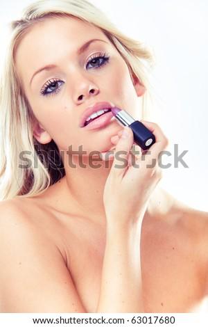 Portrait of a beautiful woman getting ready applying lipstick - stock photo