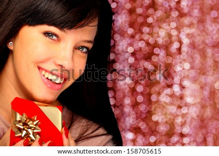 Portrait of a beautiful woman holding a gift - stock photo