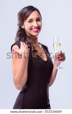 Portrait of a beautiful woman holding a glass of champagne, wearing a little black dress for new years eve party celebration