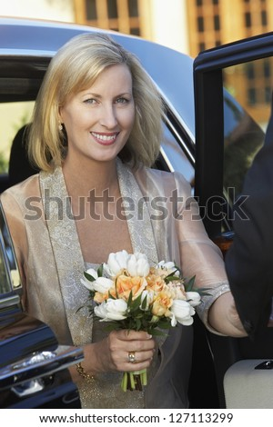 Portrait of a beautiful woman holding bouquet while getting down from car - stock photo