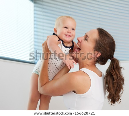 Portrait of a beautiful woman holding cute smiling baby
