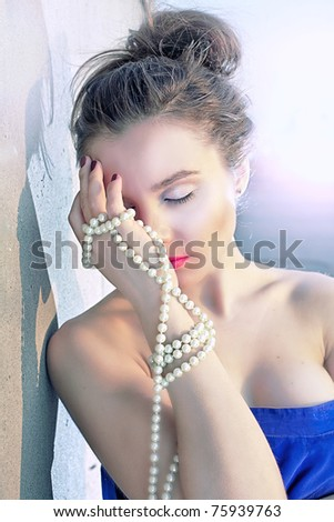 Portrait of a beautiful woman holding pearl necklace - stock photo