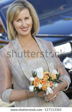 Portrait of a beautiful woman holding roses with car in the background - stock photo