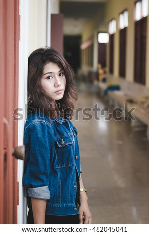 Portrait of a beautiful woman in a blue jeans shirt on the background of abandoned building
