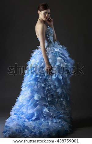 Portrait of a beautiful woman in a delicate blue dress on a dark grey background