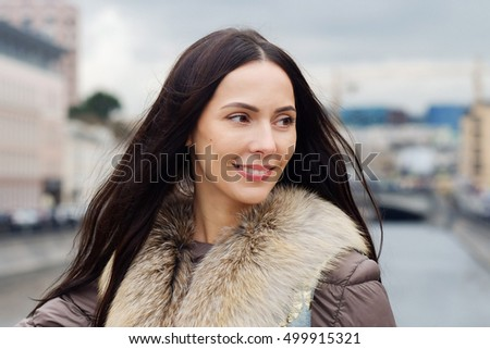 Portrait of a beautiful woman in a fur waistcoat, autumn/winter outdoors