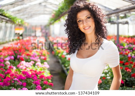 Portrait of a beautiful woman in a greenhouse - stock photo