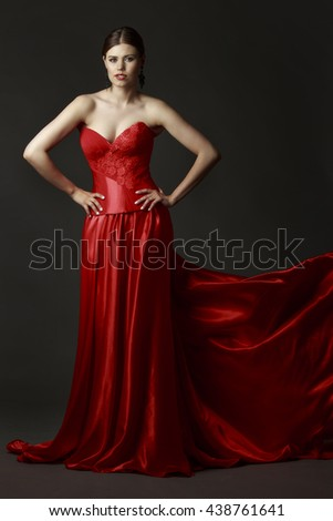 Portrait of a beautiful woman in a red dress on dark background - stock photo