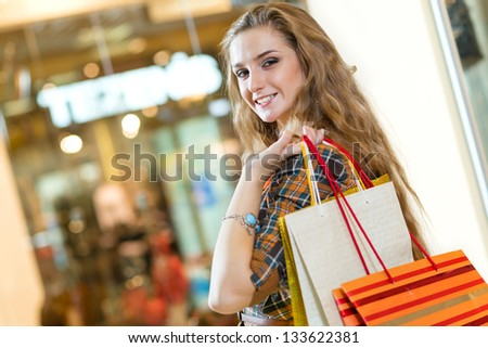 portrait of a beautiful woman in a shopping center, holding shopping bags and smiling