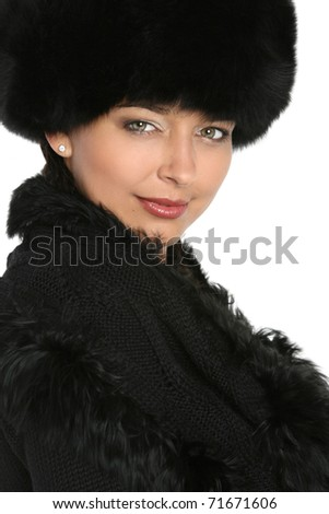 Portrait of a beautiful woman in black fur cap on a white background