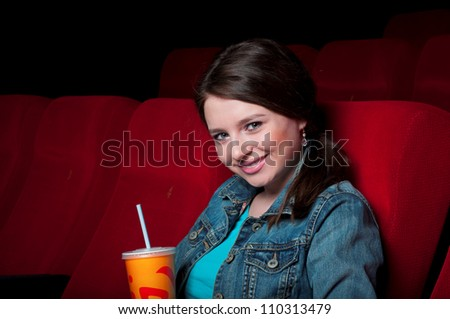 portrait of a beautiful woman in cinema, holding drinks and smiling - stock photo