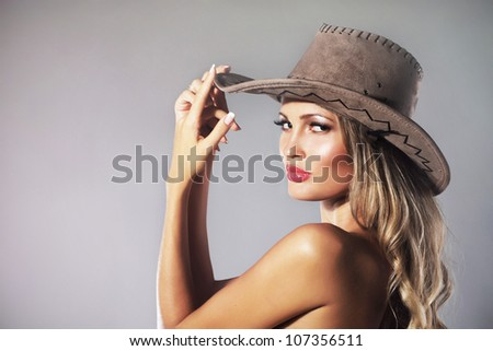 Portrait of a beautiful woman in cowboy's hat - stock photo
