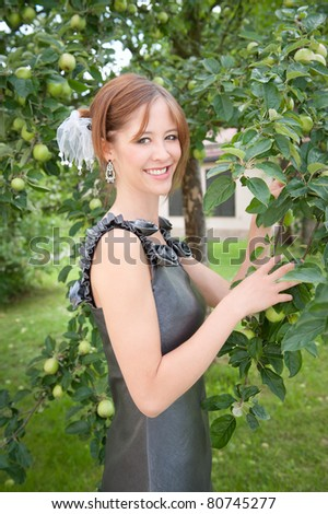 Portrait of a beautiful woman in elegant dress in front of an apple tree
