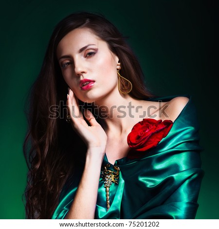 portrait of a beautiful woman in green dress whith rose