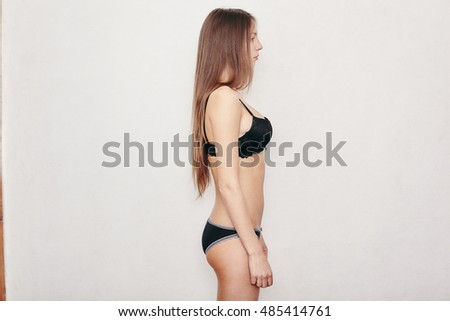 Portrait of a beautiful woman in sexy black lingerie posing on a white background