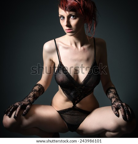 Portrait of a beautiful woman in sexy lingerie in front of black studio background - stock photo