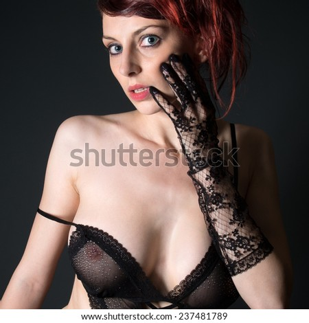 Portrait of a beautiful woman in sexy lingerie, in front of dark studio background - stock photo