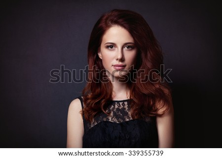 Portrait of a beautiful woman in style dress on dark background - stock photo