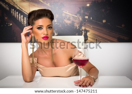 Portrait of a beautiful woman in the evening with a wine glass