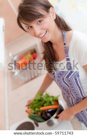 Portrait of a beautiful woman in the kitchen - stock photo
