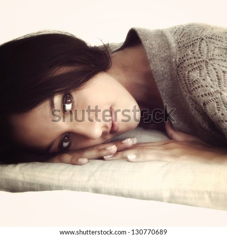 Portrait of a beautiful woman laying on a pillow