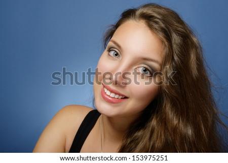 Portrait of a beautiful woman on blue. - stock photo