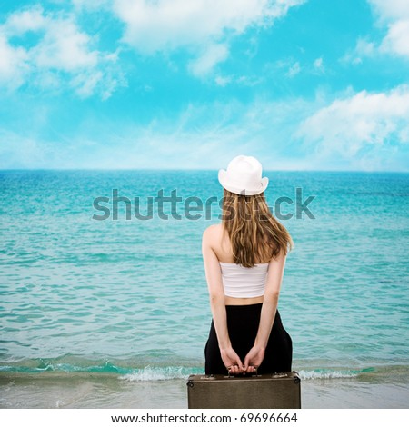 Portrait of a beautiful woman on the beach, girl with a suitcase against the sea - stock photo