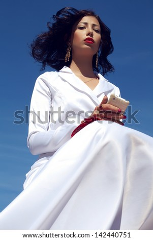 Portrait of a beautiful woman posing in elegant white atlas cocktail dress with red leather clutch holding mobile phone. Luxurious golden accessories (ring, earrings). Outdoor shot - stock photo