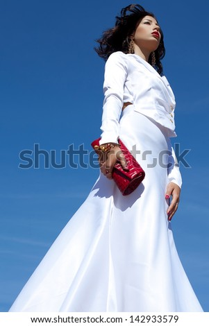 Portrait of a beautiful woman posing in elegant white atlas cocktail dress with red leather clutch in her hands over blue sky background. Luxurious golden accessories (bracelet, earrings). Copyspace - stock photo
