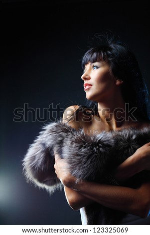 Portrait of a beautiful woman posing in studio on a dark background - stock photo