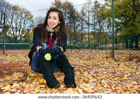 Portrait of a beautiful woman sitting in tennis court - stock photo