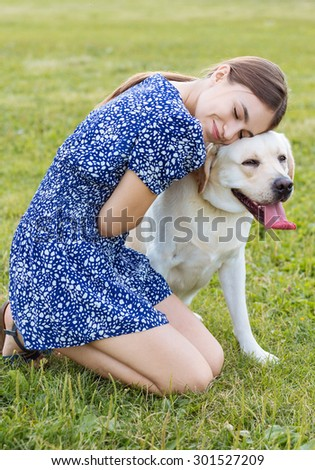 Portrait of a beautiful woman sitting on the grass with a playful young dog,and hugs her.Nature - stock photo