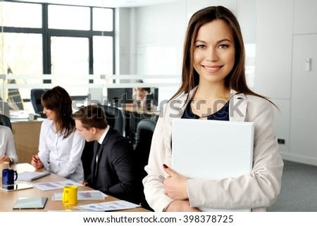 Portrait of a beautiful woman smiling at you with her colleagues in the background. - stock photo