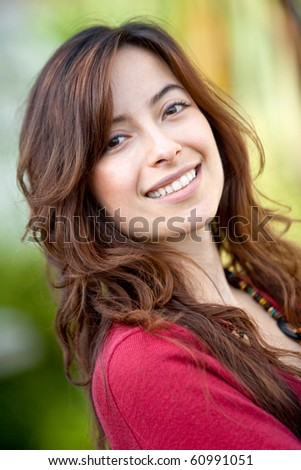 Portrait of a beautiful woman smiling outdoors - stock photo