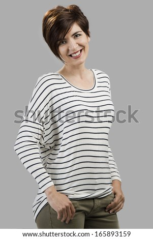 Portrait of a beautiful woman smiling, over a gray background - stock photo