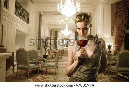 Portrait of a beautiful woman standing in a corridor of a luxury hotel with a glass of wine in her hand - stock photo