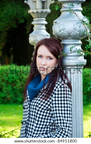 portrait of a beautiful woman standing in the park near vintage column - stock photo