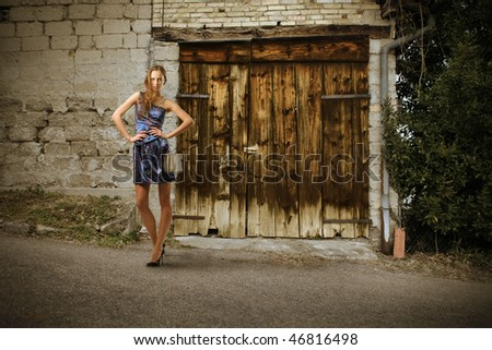 Portrait of a beautiful woman standing next to the door of an ancient house - stock photo