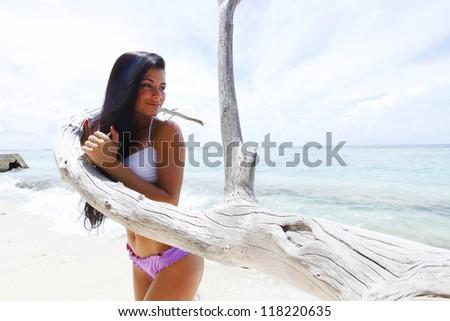 Portrait of a beautiful woman standing on beach near dry tree - stock photo