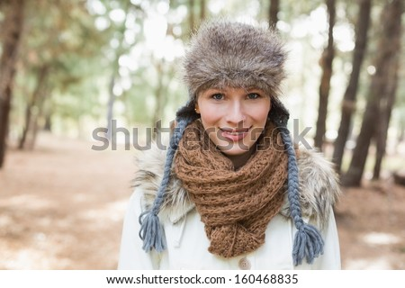 Portrait of a beautiful woman wearing fur hat with woolen scarf and jacket in the woods - stock photo