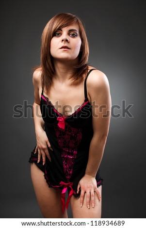 Portrait of a beautiful woman wearing negligee on gray background - stock photo