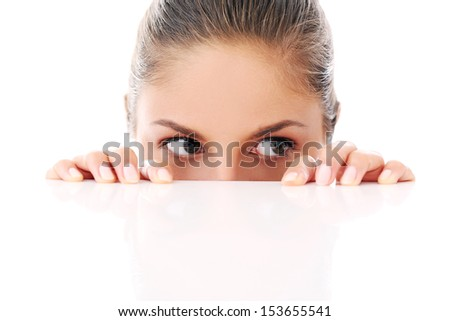 Portrait of a beautiful woman who is hiding and looks like she is playing over a white background - stock photo