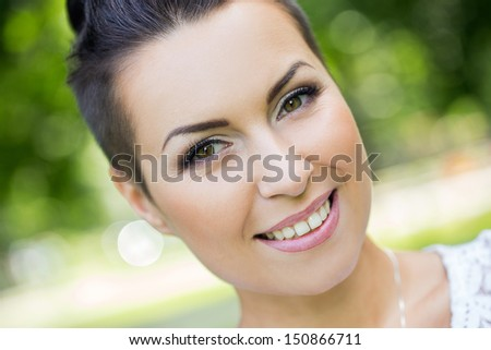 Portrait of a beautiful woman who is smiling and posing in a park